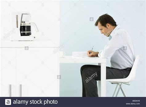 Man Sitting At A Desk Man Sitting At Desk Writing Side View Stock Photo