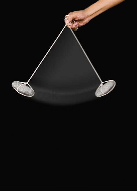 a swinging pendulum close up of a person s hand swinging a stone pendulum