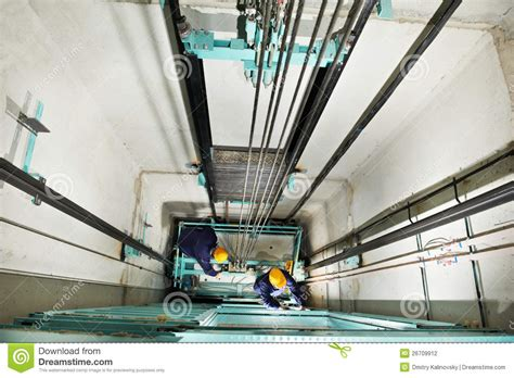 machinists adjusting lift  elevator hoistway stock photography image