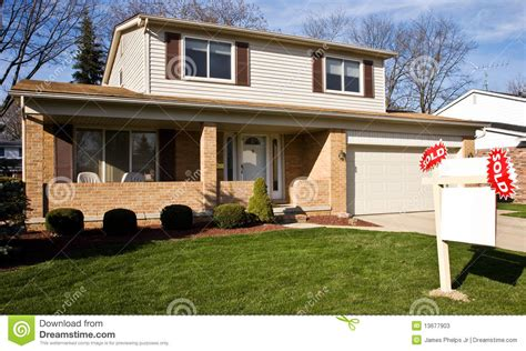 real estate sold sign in front of residential home stock