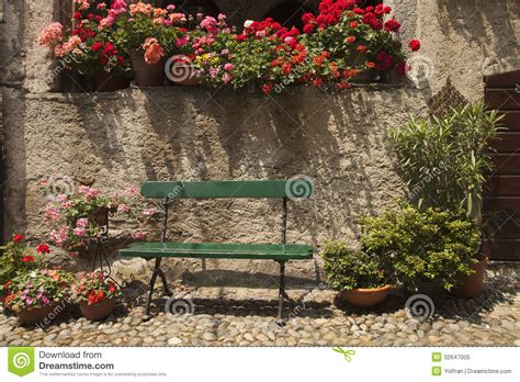green bench flowers bench with colourful geranium flower pots royalty free