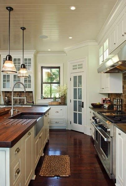 white kitchen cabinets with butcher block countertops bead board ceiling and dark hardwood in kitchen white