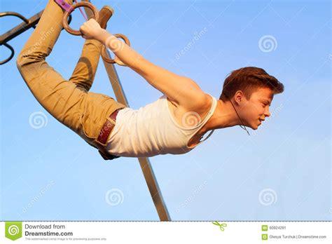 teen girl hanging upside down girl hanging upside down on gymnastics rings stock photo