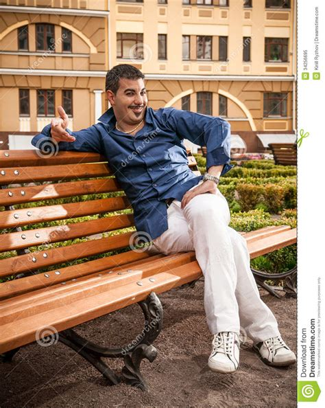 person sitting on bench macho man sitting on bench royalty free stock photo