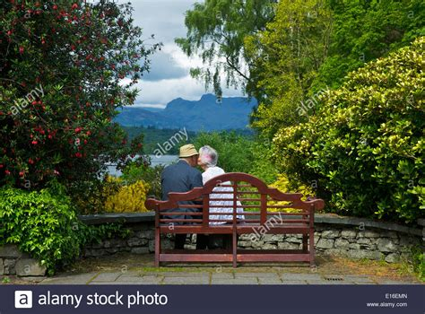 lovers on a park bench elderly couple sitting on a bench at brockhole lake