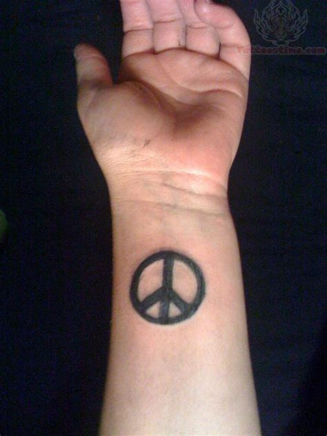 black peace sign tattoo on wrist