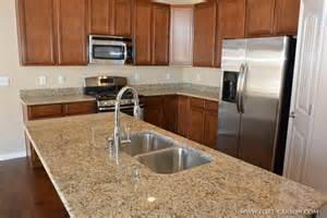 island kitchen sink a closeup view of the granite slab countertop and the