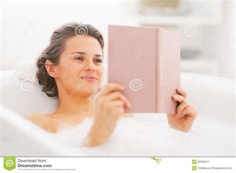 happy reading book in bathtub stock image