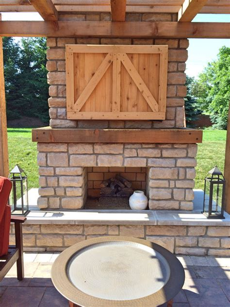 farmhouse outdoor fireplace with custom cedar tv cabinet