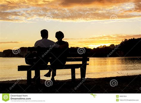 bench couple watch couple watching a beautiful sunset together stock photo image 48691854