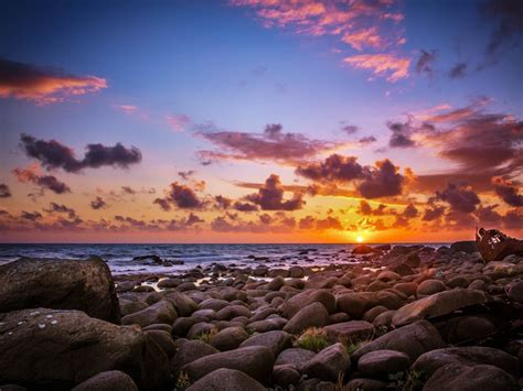 sun rays   horizon sea coast rocks  rocks