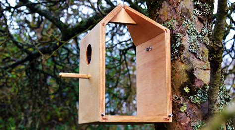 a milk carton inspired birdhouse made from recycled