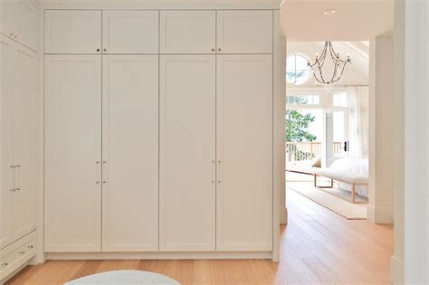 walk in closet with floor to ceiling wardrobe cabinets