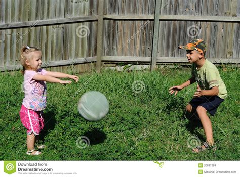 kids playing in backyard two kids playing ball in a backyard royalty free stock