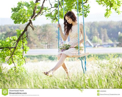 woman on a swing woman is swinging on a swing in summer forest stock photo