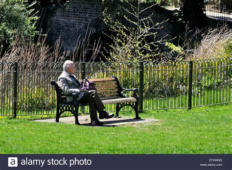 sitting in a park bench single old man sitting on bench in a sunny park stock