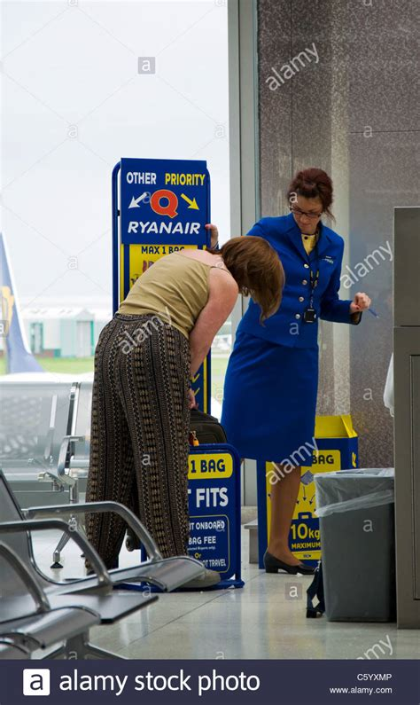 ryanair baggage size check gauge woman passenger is forced to check size of hand luggage at