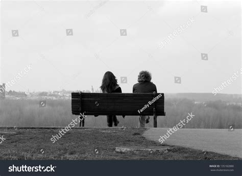 two people sitting on a bench two people sitting on bench in black and white stock photo