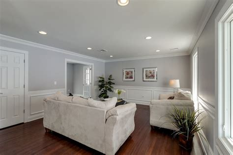 wainscoting living room living room with high ceiling crown molding in