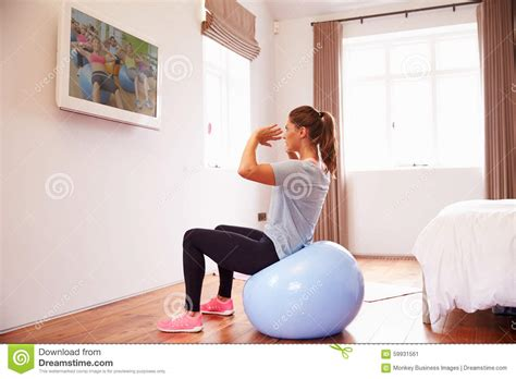 how to work out in your bedroom woman on ball working out to fitness dvd on tv in bedroom