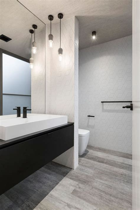 this mostly white bathroom with a black vanity has simple pendant lights hanging in the corner