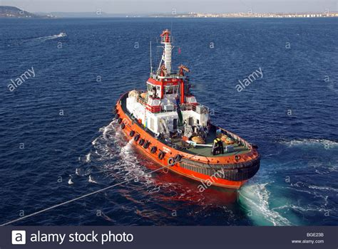 Tug Boat Shoppinf tug boat tow line pulling liner departing canakkale port in the stock photo royalty free image