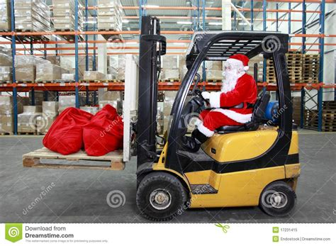 santa claus forklift operator in warehouse stock image