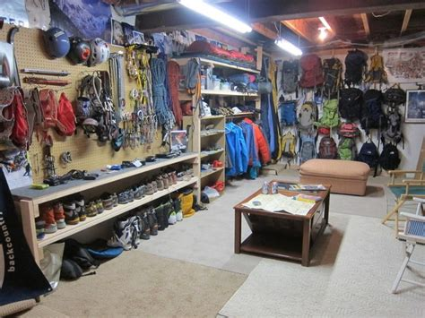 gear room gear storage heaven peg board hooks low hanging coats with shelf above and sleeping bags next