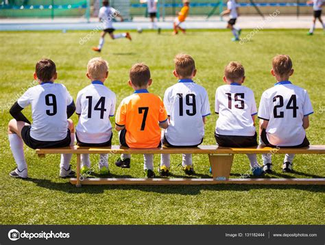 soccer player bench young football players young soccer team sitting on