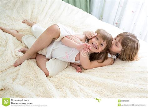 two girls kissing in bed happy little girls sisters hugging and kissing stock