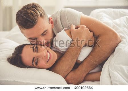 cuddling in bed meaning handsome young man hugging kissing his stock photo