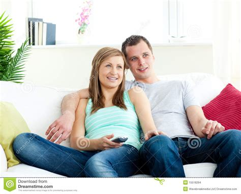 sofa for watching tv attentive young couple watching tv on the sofa stock photo