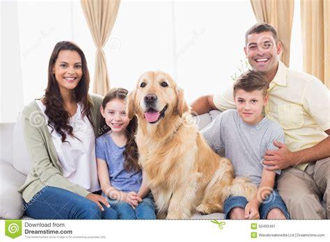 golden retriever family happy family sitting with golden retriever on sofa stock image image of golden