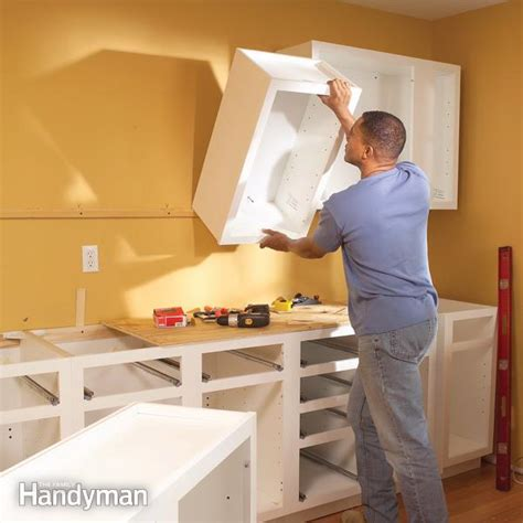how to put up kitchen cabinets how to install upper installing kitchen cabinets the family handyman