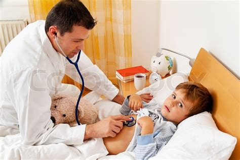 a doctor at home visits examines sick child stock photo