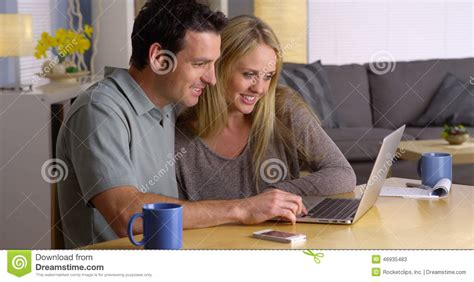 couple getaways couple looking for vacation getaways on laptop stock photo