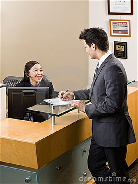 receptionist greeting at front desk stock photos