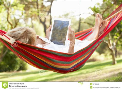 Hammock Book senior relaxing in hammock with e book royalty free