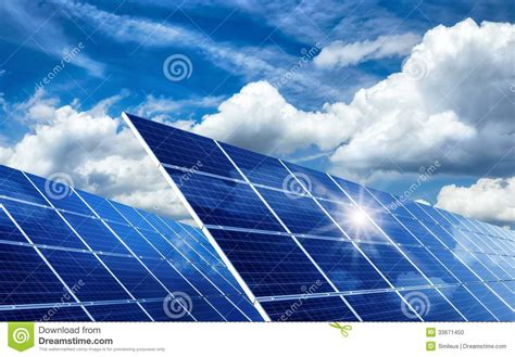 solar panels reflecting the sun and clouds stock photo