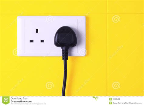 how to date a l by the plug plugged in socket against yellow tiles background stock