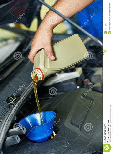 car engine service car mechanic pouring oil into motor engine stock photo