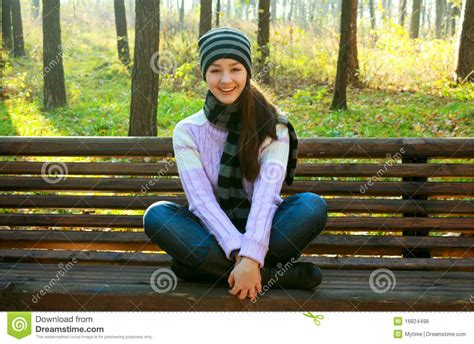 girl sitting on a bench happy young girl sitting on bench royalty free stock