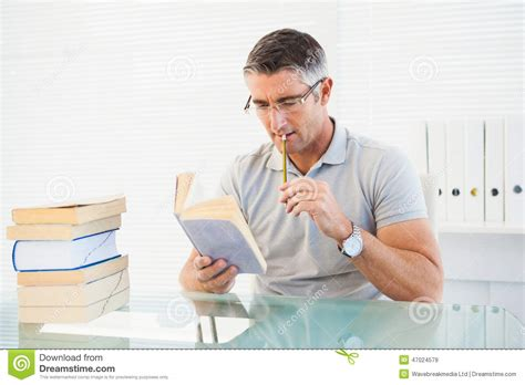 thinking in pictures book with glasses thinking and reading a book stock photo