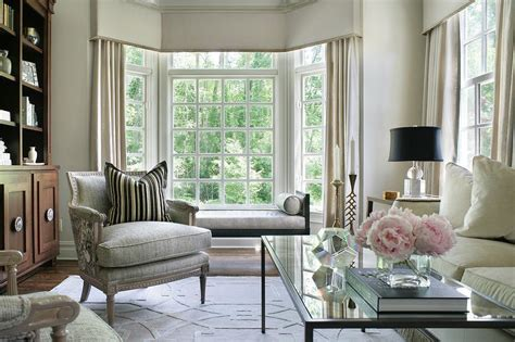 living room with bay window blue x stools with black sofa table transitional