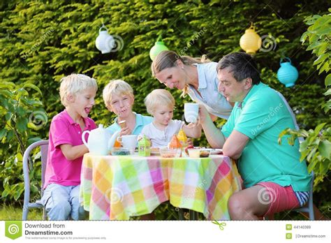 Mother Daughter House Plans parents with kids having lunch outdoors stock photo