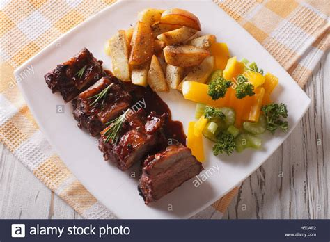 bbq pork ribs with a side dish of vegetables close up on a plate stock photo royalty free image