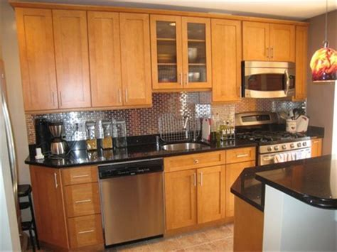 Kitchens with light wood cabinets and black countertops