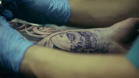 tattoo artist working man draws on his arm woman s face