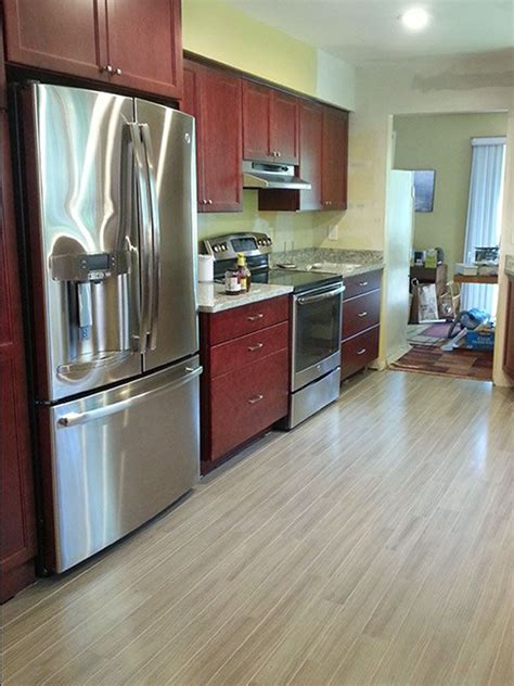 grey hardwood floors accent a modern kitchen with cherry cabinets and stainless steel appliances