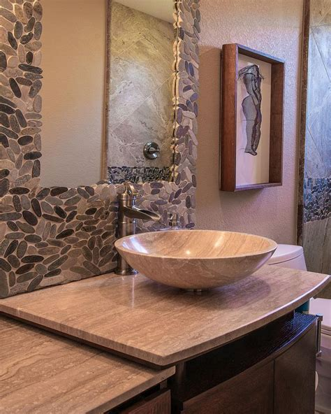 stone earth bathrooms sliced pebbles form a mosaic surrounding the mirror in